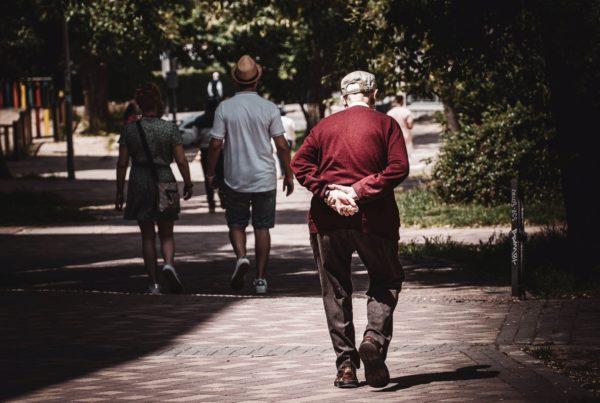 An elderly gentleman walking alone, with hands behind his back