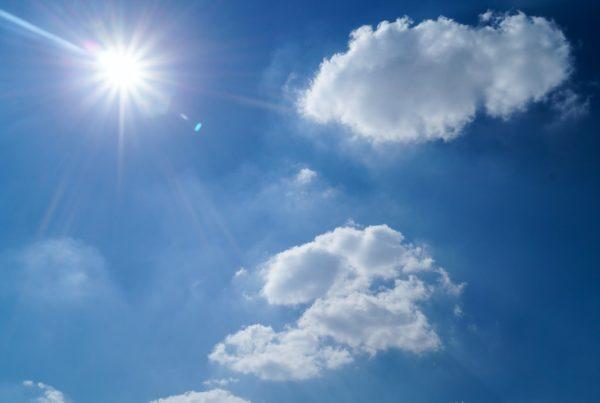 Sun shining in a blue, cloudy sky